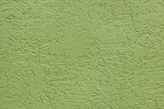 Green flat rough painted wall with many cavities. Used as a background. royalty free stock image