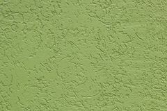 Green flat rough painted wall with many cavities. Used as a background. royalty free stock photos