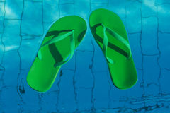 green flip flops floating in the swimming pool, top view Royalty Free Stock Image
