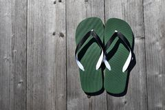 Green flip flops. On grey natural weathered wooden background top view with copy space for text stock images