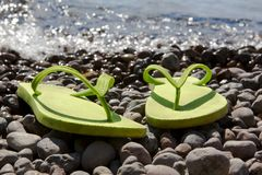 Green flip-flops on the pebble beach Stock Photo
