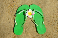 Green flip flops on the sand. Beach Royalty Free Stock Photo