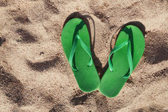 Green flip flops in the sand near the sea Stock Image