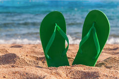 Green flip flops in the sand near the sea Stock Images