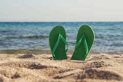 Green flip flops in the sand near the sea Stock Photo