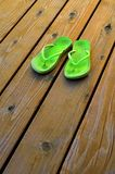 Green Flip Flops for Summer on Old Wood Deck Stock Images