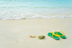 Green flipflop sandals. On sea beach stock image