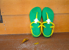 Green flipflop sandals. On wooden wall royalty free stock photos