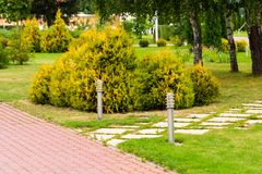 A green flowerbed in the park with a path of tiles. And full-length flashlights royalty free stock photography