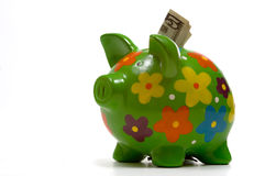 Green Flowery Piggy Bank. A five dollar American bill sticking out of the top of a flower decorated green piggy bank on a white background with copy space Royalty Free Stock Photos