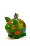 Green Flowery piggy bank with money. Green, brightly colored piggy bank with money sticking out the top on white Stock Images