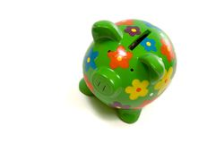 Green Flowery piggy bank with money. Green, brightly colored piggy bank with money sticking out the top on white Royalty Free Stock Photos