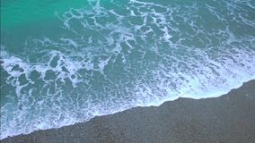 Green foamy ocean waves coming ashore, splashing on sand beach in slow motion. Stock footage stock video