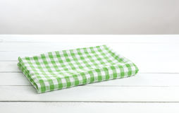 Green folded tablecloth on white table background for product montage stock photos