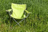 Green folding chair on the grass Royalty Free Stock Image