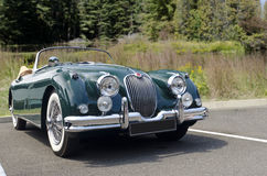 Green foreign vintage sports car with whitewall tires Stock Photos