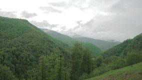 Cloud timelapse in the Caucasus mountains 002. Green forests on the background of snow-capped Caucasus mountains stock video footage