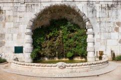Green fountain in the San Pedro de Alcantara Garden. Lisbon. Por. Green fountain in a semicircular niche in the wall of San Pedro de Alcantara Garden. Lisbon Royalty Free Stock Photo