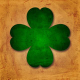 Green four-leaved shamrock in old paper background. Shamrocks - vintage beige background with green four-leaved flower over old paper Royalty Free Stock Image