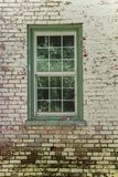Green framed pane glass window. Against weathered against white painted and red brick wall Stock Photography