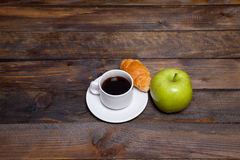Green fresh apple and coffee in white cup with croissant Stock Image