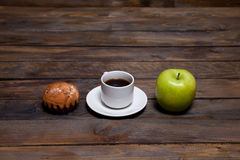 Green fresh apple and coffee in white cup with cupcake Royalty Free Stock Photos