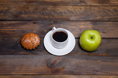 Green fresh apple and coffee in white cup with cupcake Stock Photography