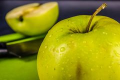 Green fresh apples, chopped up on the old board. On a wooden table. stock photos