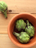 Green fresh artichoke. On the wooden table Stock Image