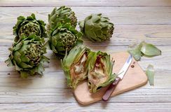 Green, fresh artichokes close-up. The green, fresh artichokes in the kitchen on a wooden table close-up Stock Photos