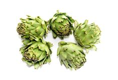 Green, fresh artichokes close-up. The green, fresh artichokes in the kitchen on a white background close-up Stock Photo