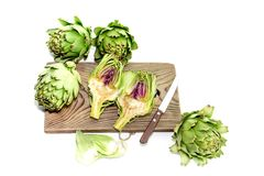 Green, fresh artichokes close-up. The green, fresh artichokes in the kitchen on a white background close-up Stock Image