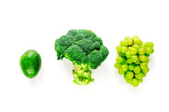 Green fresh broccoli, grape and avocado for fitness diet food on white table background top view. Green fresh broccoli, grape and avocado for fitness diet food stock photo