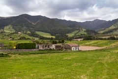 Fields and a mountain, Sao Miguel, Azores Islands. Green and fresh country surrounding a village Lomba do Pomar. Fields and a farm. Mountains in the background stock images