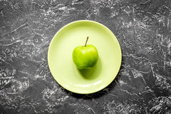 Green fresh food with apple on plate for fitness diet on dark table background top view Stock Image
