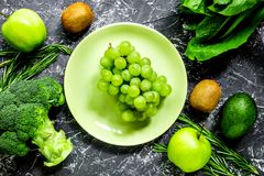 Green fresh food for fitness diet on dark table background top v. Green fresh food for fitness diet on dark kitchen table background top view Stock Images
