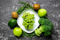 Green fresh food for fitness diet on dark table background top view. Green fresh food for fitness diet on dark kitchen table background top view Stock Photography