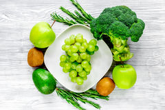 Green fresh food for fitness diet on gray wooden table background top view. Green fresh food for fitness diet on gray wooden kitchen table background top view Stock Photo