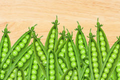 Green fresh peas over wooden background Stock Photos