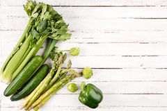 Green fresh seasonal vegetables on white wooden table background Stock Photography
