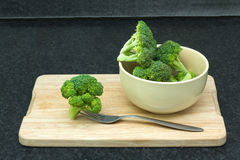 Green fresh vegetables. Broccoli with a fork in a bowl on a cutting board Stock Photo