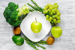Green fresh vegetables, fruits and apple on plate for healthy salad gray background top view. Green fresh vegetables and fruits and apple on plate for healthy Royalty Free Stock Photos