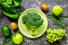 Green fresh vegetables and fruits for healthy salad on dark table background top view. Green fresh vegetables and fruits for healthy salad on dark kitchen table Stock Photo