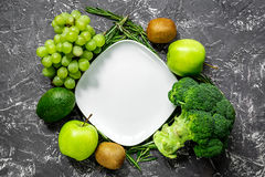 Green fresh vegetables and fruits for healthy salad on dark table background top view. Green fresh vegetables and fruits for healthy salad on dark kitchen table Royalty Free Stock Photography