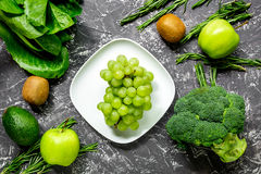 Green fresh vegetables and fruits for healthy salad on dark table background top view Stock Photo