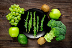 Green fresh vegetables and fruits for healthy salad on wooden table background top view. Green fresh vegetables and fruits for healthy salad on wooden kitchen Royalty Free Stock Photo