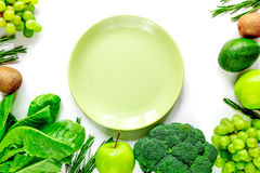 Green fresh vegetables, fruits and plate for healthy salad white background top view mock up. Green fresh vegetables and fruits and plate for healthy salad on royalty free stock images