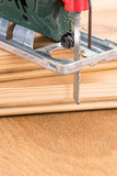Green fretsaw on wooden plank Stock Photos