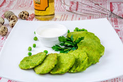 Green fritters, peas and parsley stock photography