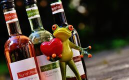 Green Frog With Red Heart Figurine Beside Glass Bottles Stock Images